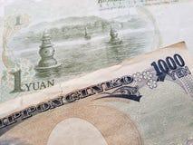 acercamiento al billete de banco chino de un yuan y al billete de banco japonés de 1000 yenes imagen de archivo libre de regalías
