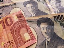 acercamiento al billete de banco europeo de diez euro y a los billetes de banco japoneses de 1000 yenes imagen de archivo libre de regalías