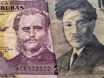 acercamiento al billete de banco Honduran de dos lempiras y al billete de banco japonés de 1000 yenes imagenes de archivo