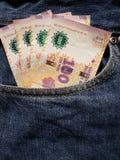 acercamiento al bolsillo delantero de vaqueros en azul con los billetes de banco de Argentina fotos de archivo