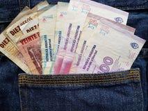 acercamiento al bolsillo trasero de vaqueros en azul con los billetes de banco de Argentina imágenes de archivo libres de regalías