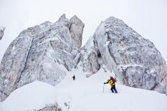Acercamiento de dos escaladores a una cara escarpada del invierno Imagenes de archivo