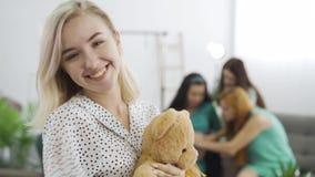 Acercamiento de una joven rubia sosteniendo al oso de peluche y sonriendo. Compañía de sus amigos sentados en el fondo y metrajes