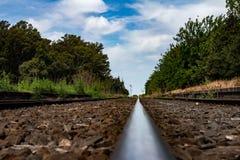 Acercamiento de una vía del tren que se pierde en infinito fotos de archivo libres de regalías
