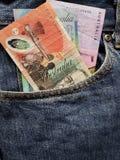 acercamiento para afrontar el bolsillo de vaqueros en azul con los billetes de banco australianos imagen de archivo