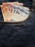 acercamiento para afrontar el bolsillo de vaqueros en azul con los billetes de banco brasileños imagen de archivo