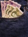 acercamiento para afrontar el bolsillo de vaqueros en azul con los billetes de banco chinos imagenes de archivo