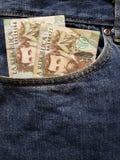 acercamiento para afrontar el bolsillo de vaqueros en azul con los billetes de banco colombianos imágenes de archivo libres de regalías