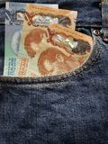 acercamiento para afrontar el bolsillo de vaqueros en azul con los billetes de banco de Nueva Zelanda imagenes de archivo