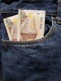 acercamiento para afrontar el bolsillo de vaqueros en azul con los billetes de banco peruanos foto de archivo