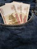 acercamiento para afrontar el bolsillo de vaqueros en azul con los billetes de banco rusos imagen de archivo libre de regalías