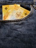 acercamiento para afrontar el bolsillo de vaqueros en azul con los billetes de banco suizos imagenes de archivo