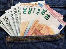 acercamiento para apoyar el bolsillo de vaqueros en azul con los billetes de banco europeos foto de archivo