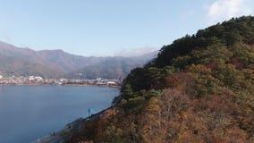 Acercamiento y subida aéreos del agua sobre la colina que revela Kawaguchiko en hojas del lago y de otoño fuji cinco almacen de video