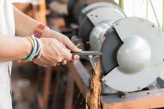 Acero de acero de Grinding de la amoladora para conseguir la agudeza fotografía de archivo