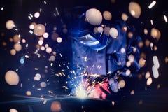 Acero de la soldadura del empleado con las chispas usando el soldador del mag del mig Fotos de archivo libres de regalías