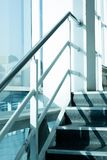 acero inoxidable de la escalera encima de la compañía luz del sol en la ventana fotografía de archivo libre de regalías