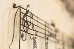 Acero viejo de la clave de G en la pared vieja con la falta de definición de la nota de la música en backg Imagen de archivo libre de regalías