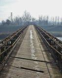 Acero viejo y puente de madera en el medio del campo Fotos de archivo