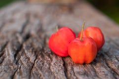 Acerolafrucht auf hölzernem Hintergrund Stockbild