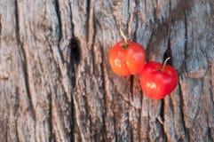 Acerolafrucht auf hölzernem Hintergrund Stockbilder