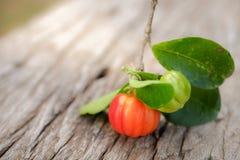 Acerolafrucht auf hölzernem Hintergrund Lizenzfreie Stockbilder