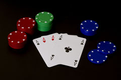 Aces. Four aces surrounded by gambling chips on a black background Royalty Free Stock Images