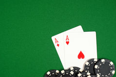 Aces with chips. Poker hand, pocket aces  with black  chips on green felt Stock Images