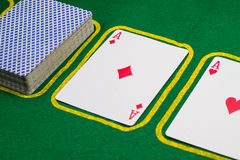 Aces and a deck on a green cloth Stock Photos