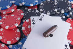 Aces poker and chips and bullet. Black aces poker and chips center close up bullet gun right center Stock Photos