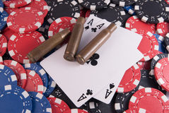 Aces poker and chips and casing bullet. Black aces poker and chips center close up casing bullet gun center Stock Images