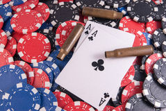 Aces poker and chips and casing bullets. Black aces poker and chips center close up casing bullet gun center Stock Photography