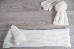Acessório feito malha do tempo frio na tabela Chapéu branco, fundo de madeira cinzento das luvas da formiga do lenço Vista superi Imagem de Stock