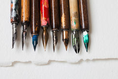 Acessórios caligráficos, coleção retro da pena de fonte do estilo Penas coloridas envelhecidas do artista, Livro Branco textured Fotografia de Stock Royalty Free