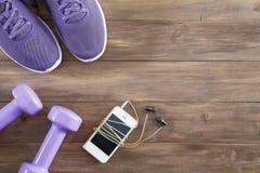 Acessórios colocados plano da aptidão da vista superior em um fundo de madeira Telefone esperto, pesos roxos, tênis de corrida ro fotografia de stock