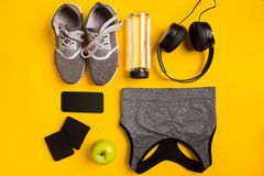 Acessórios da aptidão no fundo amarelo As sapatilhas, a garrafa da água, os fones de ouvido e o esporte cobrem fotografia de stock