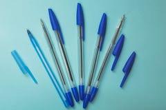 Acessórios da escola, penas azuis em um fundo azul foto de stock