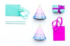 Acessórios da festa de anos Caixa de presente, saco de papel, chapéu do partido no espaço branco da cópia da opinião superior do  Fotos de Stock
