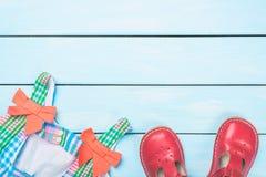 Acessórios da menina Vestido colorido e sapatas vermelhas na luz - fundo pastel de madeira azul Vista superior Foto de Stock