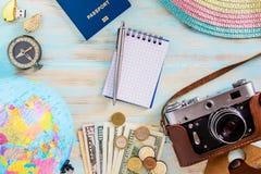 Acessórios do curso no compasso velho do photocamera do fundo de madeira azul com passaporte e dólares fotografia de stock royalty free