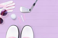 Acessórios do golfe para mulheres em uma superfície de madeira no roxo fotos de stock