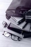 Acessórios do homem de negócios e saco do caderno na mesa Fotografia de Stock