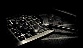 Acessórios do negócio (lente de aumento, calculadora) e gráficos, tabelas, cartas em uma tabela com fundo escuro Foco seletivo Fotos de Stock Royalty Free