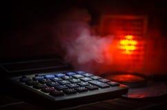 Acessórios do negócio (lente de aumento, calculadora) e gráficos, tabelas, cartas em uma tabela com fundo escuro Foco seletivo Fotos de Stock