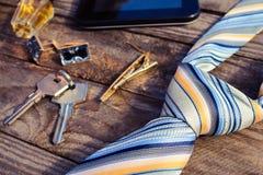 Acessórios dos homens: laço, botão de punho, tabuleta, perfume e chaves no fundo de madeira velho Imagens de Stock