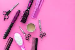 Acessórios profissionais do cabeleireiro no espaço da opinião superior do fundo do rosa da mesa do trabalho para o texto imagem de stock