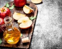 Aceto di sidro di Apple con le mele fresche sul tagliere Fotografie Stock