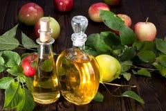 Aceto di sidro di Apple in una nave di vetro ed in mele Immagine Stock