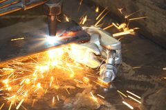 Acetylene heat blast. Acetylene blow torch blasting through a piece of metal with intense heat from the blue flame, with sparks flying and hot blobs of metal Stock Photography