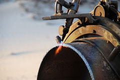 Acetylene torch and iron pipe. An acetylene torch finishes cutting a pipe.  Beads of molten metal visible near the flame Stock Image